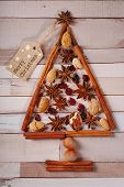 foto of hazelnut tree  - christmas tree made of spices and nuts on old wooden background - JPG