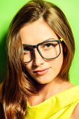 pic of spectacles  - Beauty portrait of a positive young woman in spectacles and bright yellow dress over green background - JPG