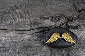 picture of bereavement  - Golden angel wings on a black stone with grey wooden background - JPG