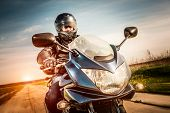 foto of biker  - Biker in helmet and leather jacket racing on the road - JPG
