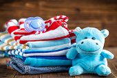 foto of child-birth  - Baby clothes stack on a wooden table - JPG