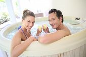 stock photo of hot-tub  - Romantic couple drinking cahmpagne in hot tub - JPG