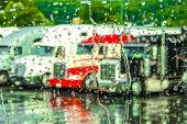picture of 18 wheeler  - Rain streaming down a window with 18 wheeler trucks in the background - JPG