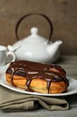 foto of eclairs  - Tasty eclairs and pot of tea on wooden table - JPG
