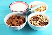 stock photo of cereal bowl  - Various sweet cereals in ceramic bowls and bowl with milk on color wooden background - JPG