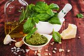 stock photo of basil leaves  - Basil pesto fresh basil leaves garlic pamrmigiano cheese olive oil and pine seeds on wooden background - JPG