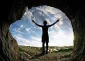 foto of cave woman  - Silhouette of a girl standing in front of the entrance to the cave - JPG