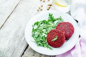 picture of quinoa  - chickpeas quinoa and beet burgers with arugula on a white wood background - JPG