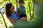 stock photo of attitude boy  - little boy plays with his mother in the forest - JPG