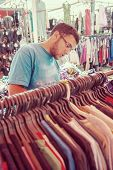 stock photo of thrift store  - Young man buying in second hand store - JPG