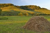 image of haystack  - Haystack in the field on a background of hills - JPG