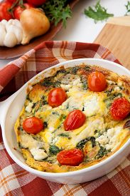 stock photo of baby goat  - Closeup of pan with fresh made frittata with baby kale sundried tomatoes and goat cheese - JPG