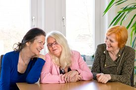 picture of reunited  - Three Happy Reunited Adult Female Friends in Trendy Outfits Sitting at the Wooden Dining Table and Laughing While Someone is Joking - JPG