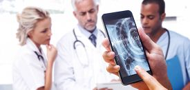 image of x-files  - hand holding smartphone against three doctors using a tablet - JPG