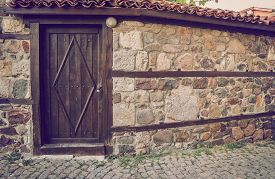stock photo of old stone fence  - Old wooden door in the stone wall - JPG