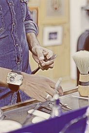 picture of barber razor  - hands of a barber holding a razor on a beard shaving session on his barber shop  - JPG