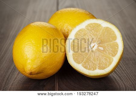poster of fresh lemons on the brown table. ripe lemons on the wooden background. fresh lemon sliced in half. juicy lemons for healthy diet