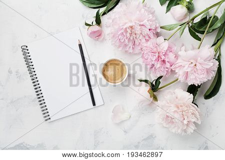 poster of Morning coffee mug for breakfast empty notebook pencil and pink peony flowers on white stone table top view in flat lay style. Woman working desk.