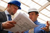 stock photo of engineering construction  - Two construction workers in hardhats looking at blueprints - JPG