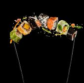 Sushi pieces placed between chopsticks, separated on black background. Popular sushi food. Very high poster
