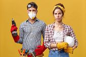 Repair, Building, Renovation And Home Concept. Serious Couple Doing Repair At Home Standing Against poster