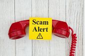 Scam Alert Message On Sticky Note On Retro Red Phone Handset On Weathered Whitewash Textured Wood Ba poster