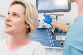 Patient in recovery room of modern hospital with nurse in background checking equipment  poster