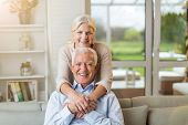 Portrait of happy senior couple sitting on sofa at home  poster