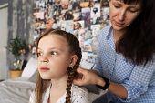 Mom Carefully Braids Her Beloved Daughters Hair In Braids On Her Head. poster
