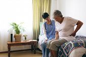 Side view of Asian female doctor and senior female patient interacting with each other at retirement poster