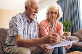 Front view of senior Caucasian couple looking at bill while sitting in retirement home poster