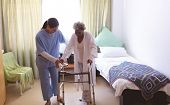 Front view of mixed race female nurse helping senior  mixed race female patient to stand with walker poster