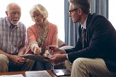 Side view of matured Caucasian male physician interacting with senior Caucasian couple at retirement poster