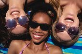 Close-up of happy beautiful young multi ethnic women with sunglasses lying on beach in the sunshine poster