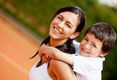 stock photo of young adult  - Lovely portrait of a mother and son at the tennis court - JPG