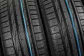 Studio Shot Of A Set Of Summer Car Tires On Black Background. Tire Stack Background. Selective Focus poster