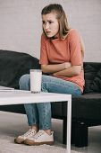 Blonde Woman With Lactose Intolerance Holding Stomach Near Glass Of Milk While Sitting On Sofa poster