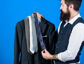 Shopping For Business Attire. Bearded Shopper Matching Necktie To Coat In Shopping Mall. Hipster Sho poster