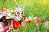 Cherry Juice In A Jar And Wicker Picnic Basket With Food On Red Blanket. Summer Picnic On Grass In A poster