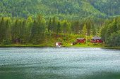 Cottage On Shore Of Fjord In Norwegian Style. Traditional Norwegian House Of Red Color. Environmenta poster