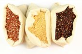 foto of quinoa  - Seeds of Red White and Black Organic Quinoa in sacks from white fabric over white background - JPG
