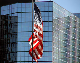 picture of modern building  - American Stars and Stripes flag flying outside skyscraper building - JPG