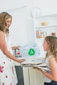 stock photo of take responsibility  - Smiling mother taking old newspaper from daughter for recycling - JPG