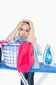 Woman getting rustrated over amount of ironing to do and leaning on basket