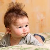 picture of mohawk  - Portrait of a baby 4 months old lying on his belly with mohawk hairstyle - JPG