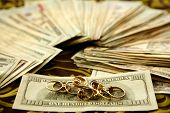 pic of white gold  - Dollar notes and gold rings over tablecloth studio recreation