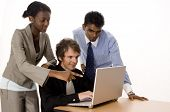 stock photo of computer technology  - three people working on a silver laptop computer - JPG