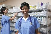 pic of medical supplies  - Portrait of female doctor nurse standing by shelves with medical supplies in background - JPG