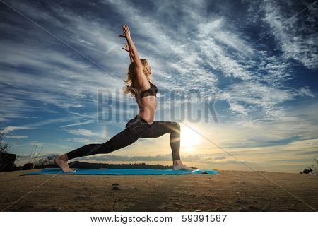 Woman practicing Warrior yoga pose outdoors over sunset sky background.  poster