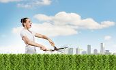 stock photo of grass-cutter  - Young happy businesswoman cutting bush with grass cutter - JPG
